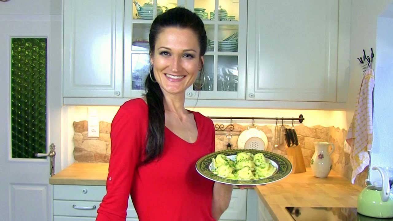 Lana hält einen Teller mit fertigen Kaerntner Kasnudeln.