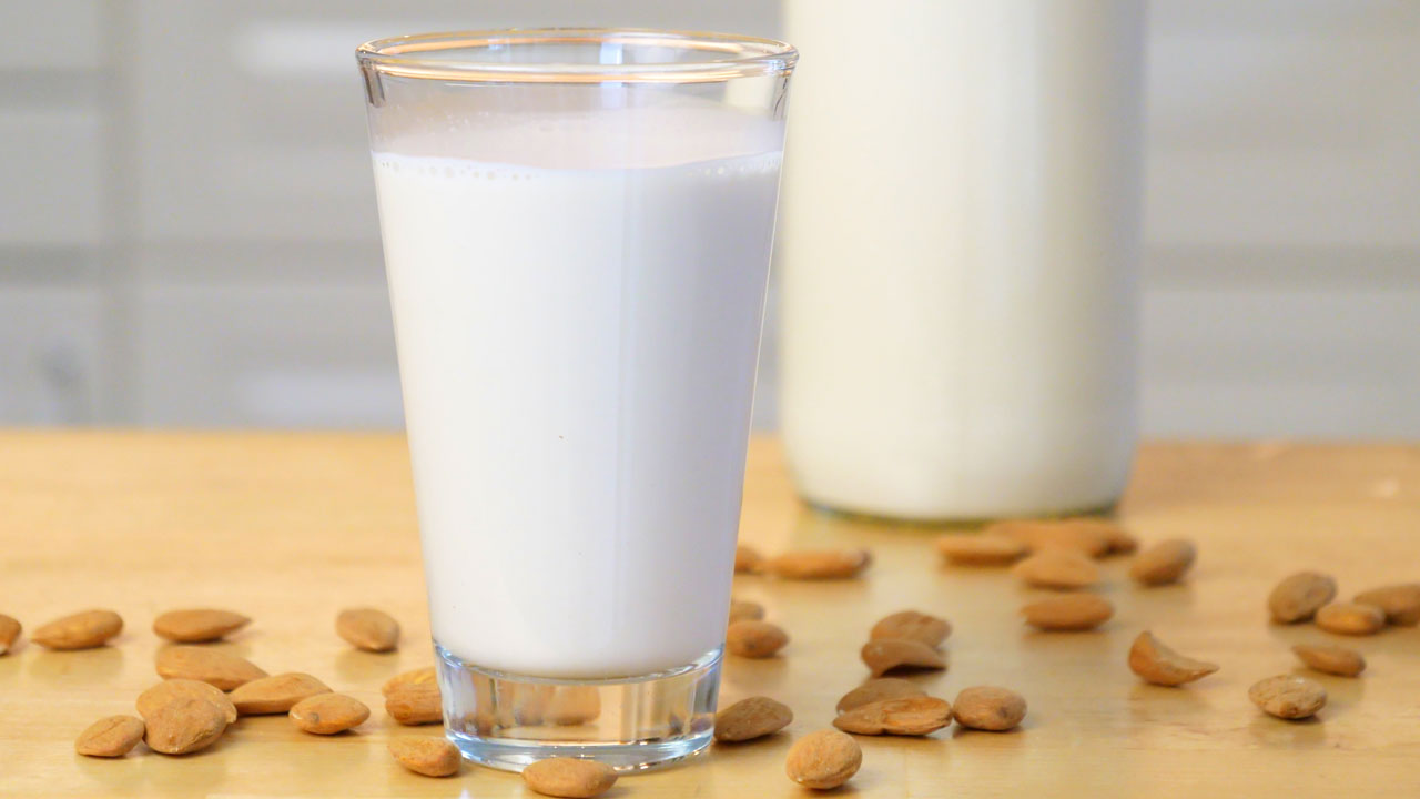 Frisch gemachte Mandelmilch in einem Glas, daneben liegen Mandeln und im Hintergrund sieht man die Mandelmilch in einer Glasflasche abgefüllt.