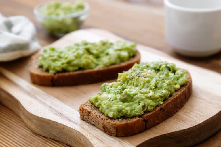 Ein Gurken-Avocado-Aufstrich auf einem Brot auf einem Brett